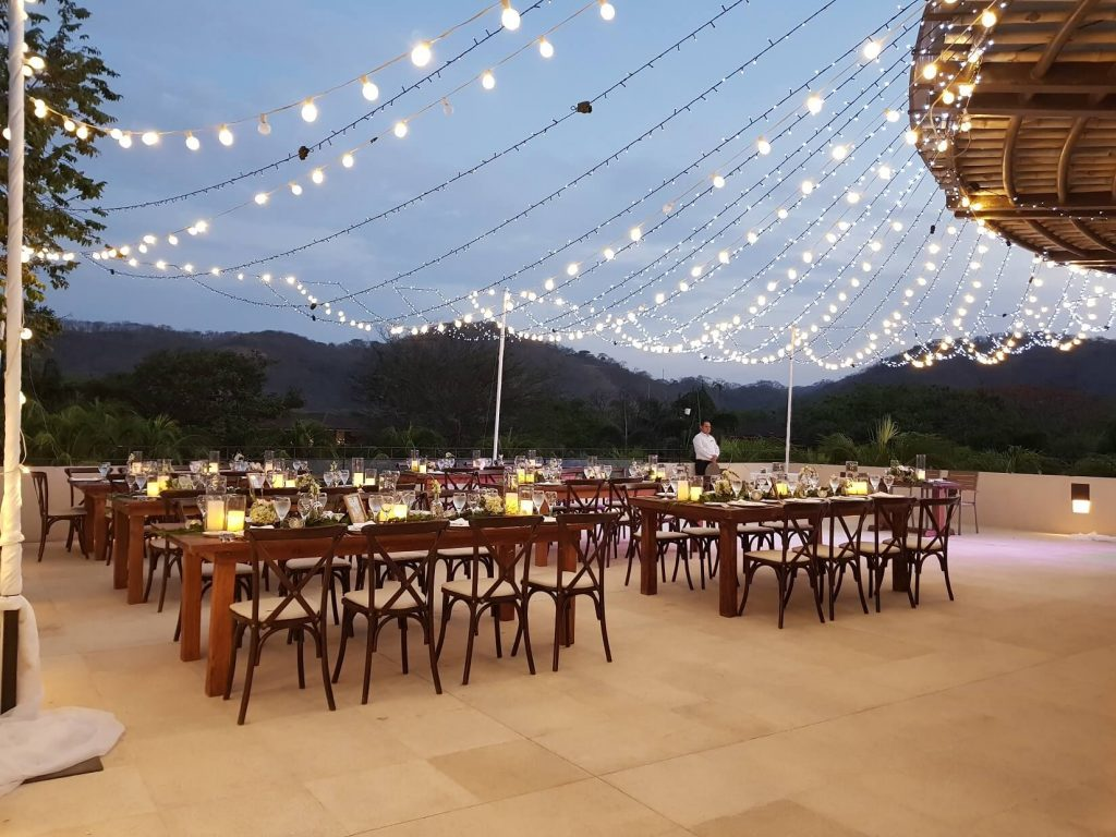 rooftop area set for a wedding reception with string lights and crossback wooden chairs
