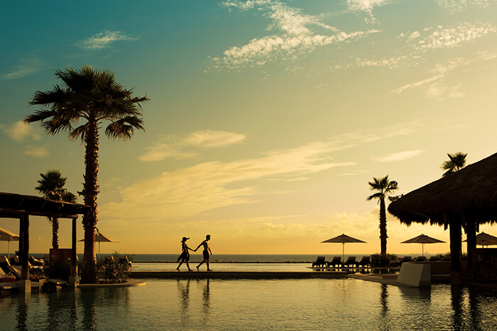 couple at sunset at the secrets playa mujeres infinity pool