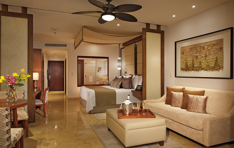 junior suite with a king bed and integrated living area at the Secrets Playa Mujeres