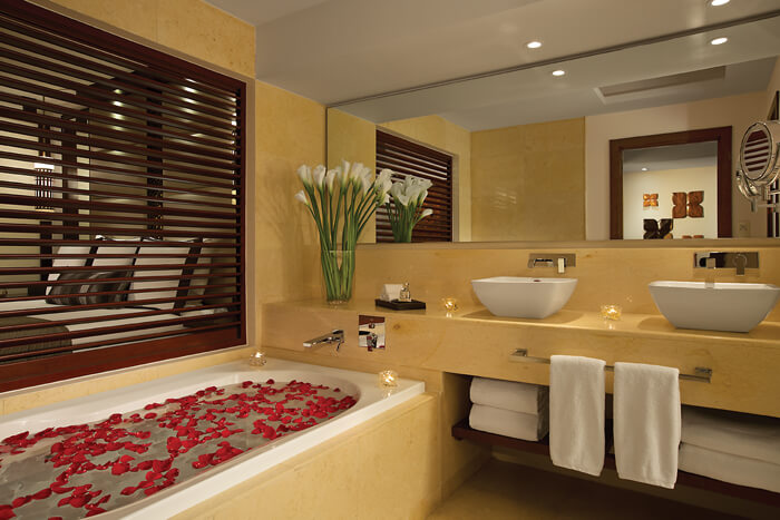 junior suite bathroom with rose petals in the tub Secrets Playa Mujeres