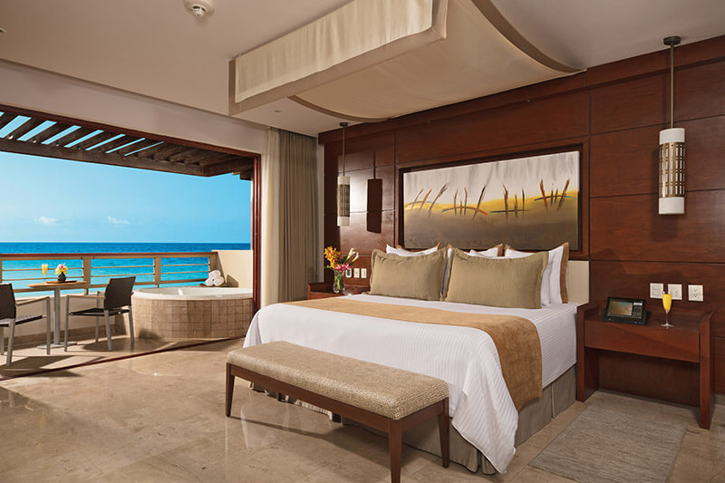 ocean front junior suite with a king bed and a jacuzzi on the balcony at the secrets playa mujeres