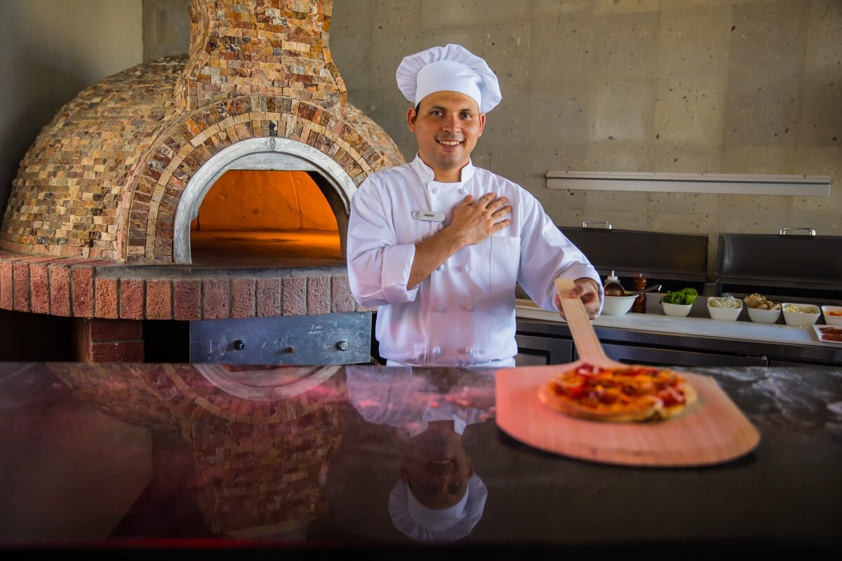 chef in front of the wood burning pizza oven at the Hyatt Ziva Los Cabos