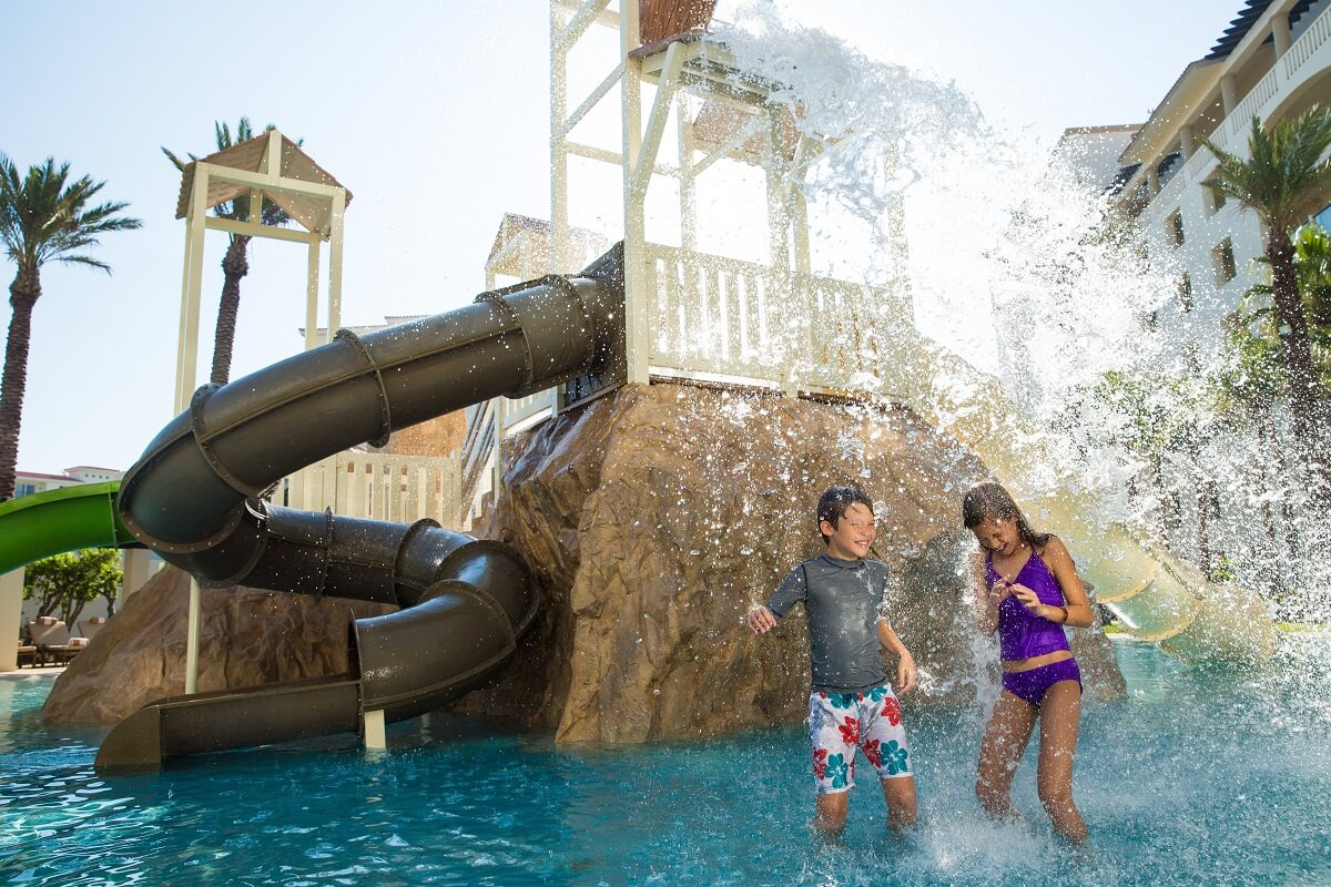 two kids playing in the waterpark fountain at the Hyatt Ziva Los Cabos