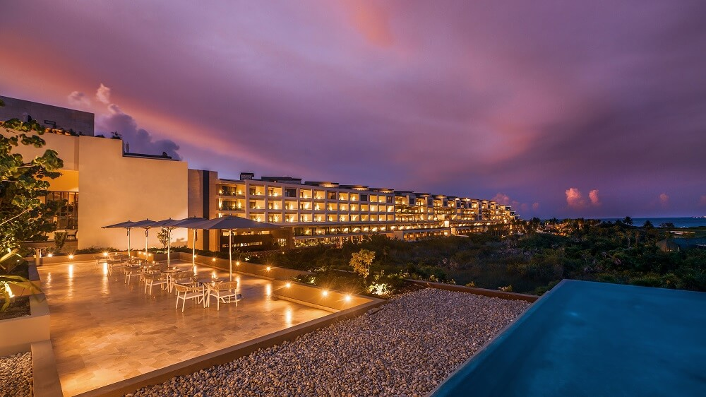 view of the lobby terrace and main building at dusk, atelier playa mujeres