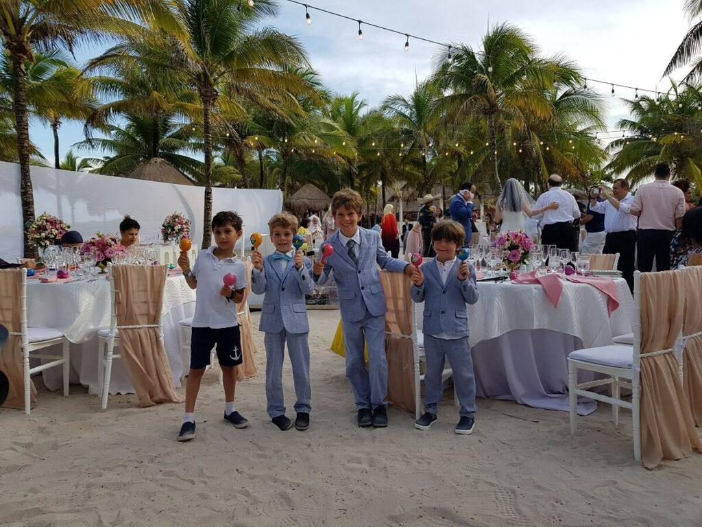 children in suits holding maracas at a destination wedding