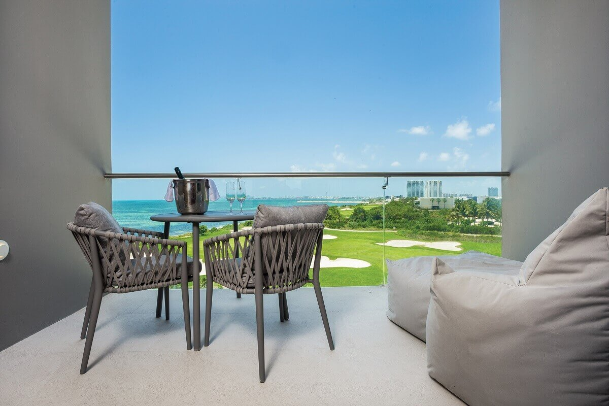 render of the balcony view overlooking the golf course and ocean at dreams vista cancun