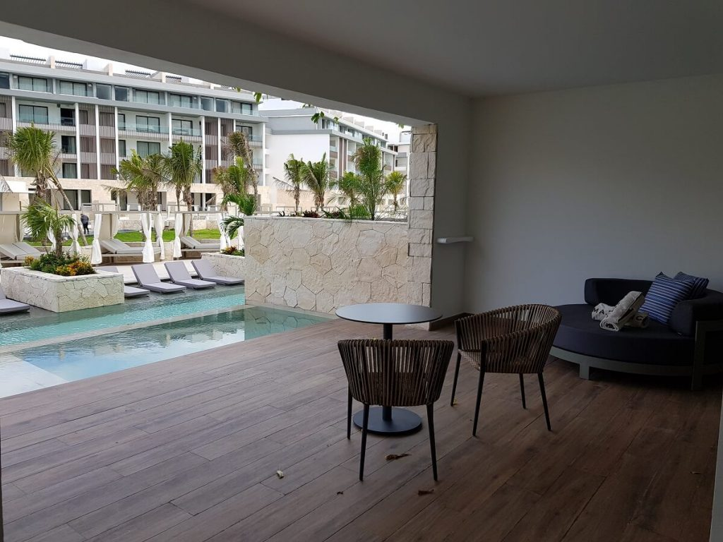 swim up room terrace with lounger bed and pool view at the majestic elegance costa mujeres