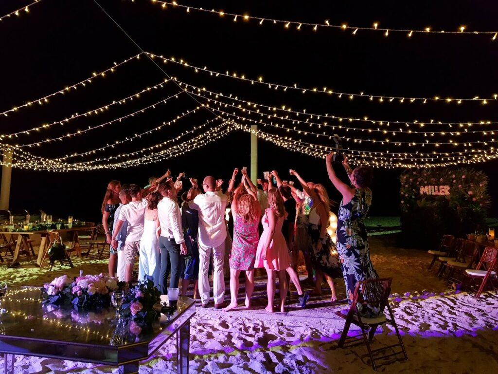 destination wedding group celebrating on the beach