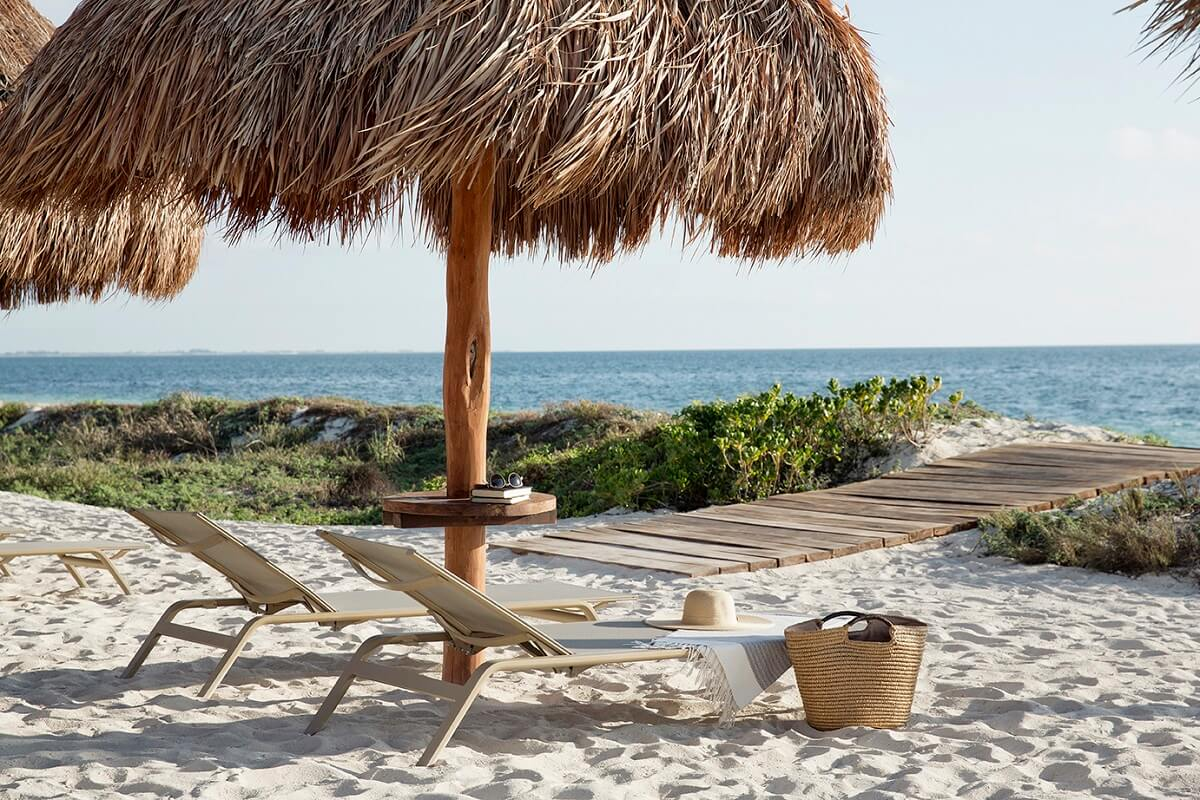 beach loungers and palapa on white sand