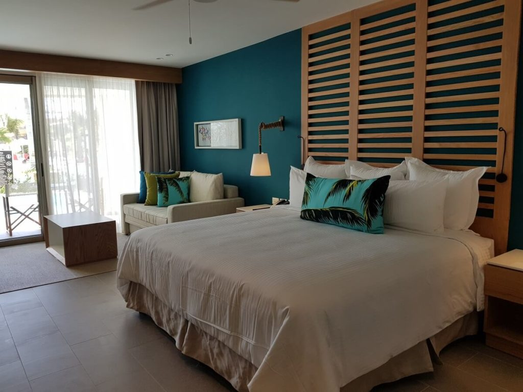 junior suite with king bed and sofa at the now natura riviera cancun