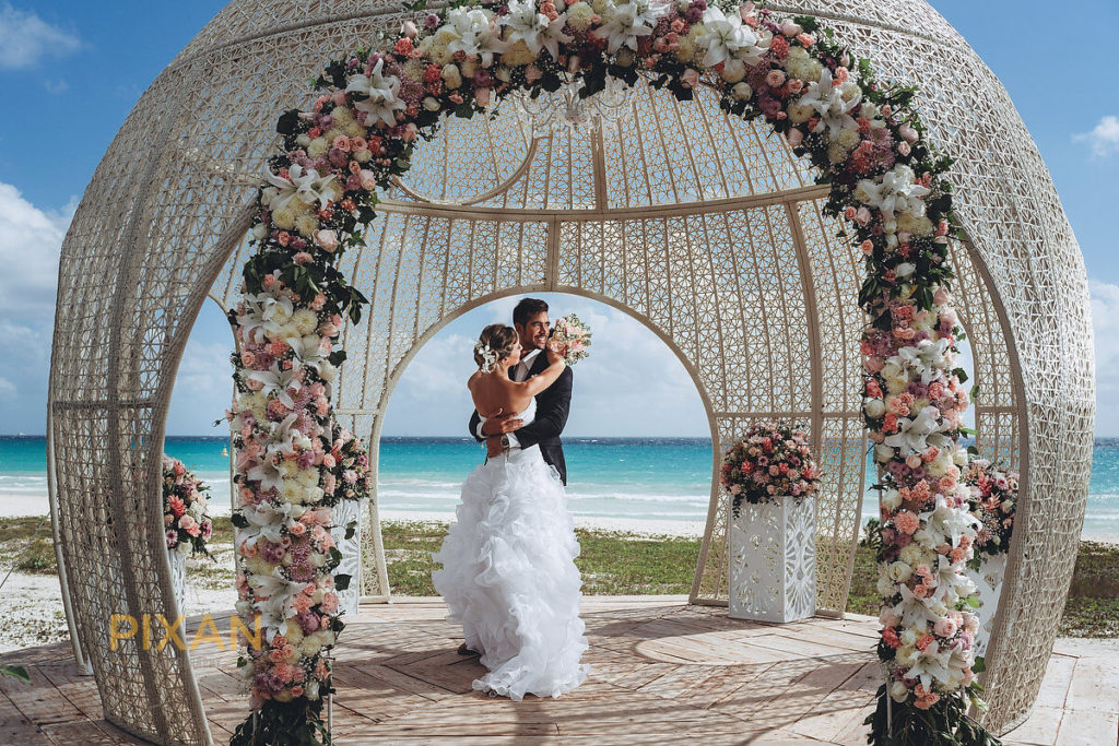 unique wedding gazebo with bride, groom and many florals overlooking the ocean at sandos hotel