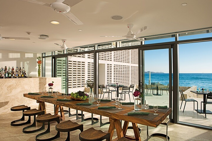 oceanview restaurant with solid wood tables at the breathless hotel in los cabos