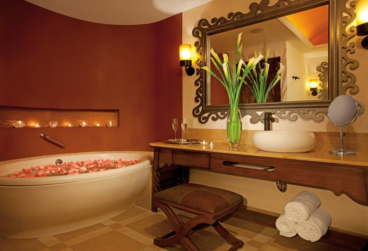 bathroom area with large mirror and bathtub with rose petals