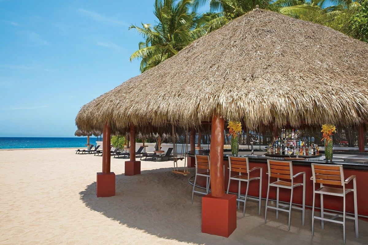 beach bar with thatched roof and high stools at dreams villamagna
