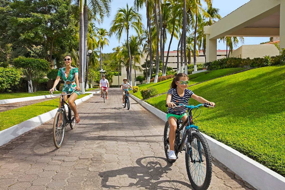 family of 4 on bicycles in a tropical area