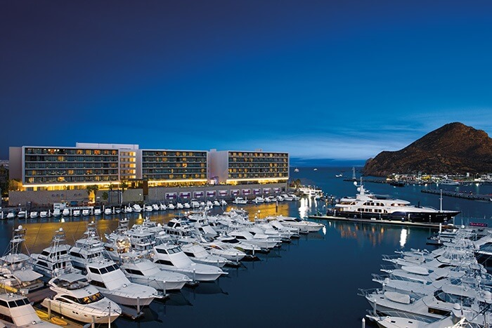 view of the marina and the breathless cabo san lucas hotel at dusk