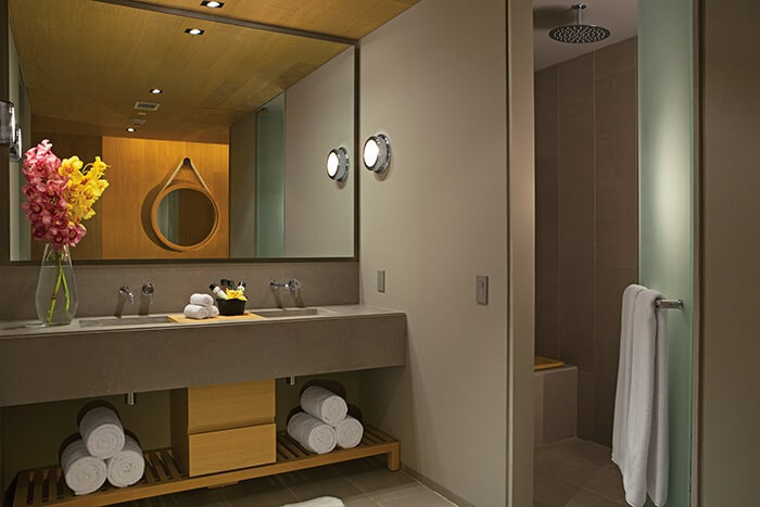 bathroom area of a junor suite with double vanity sinks and a large mirror