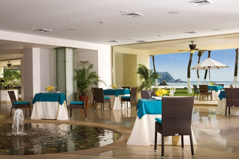 interior of a restaurant with a fountain, tables for two and an ocean view