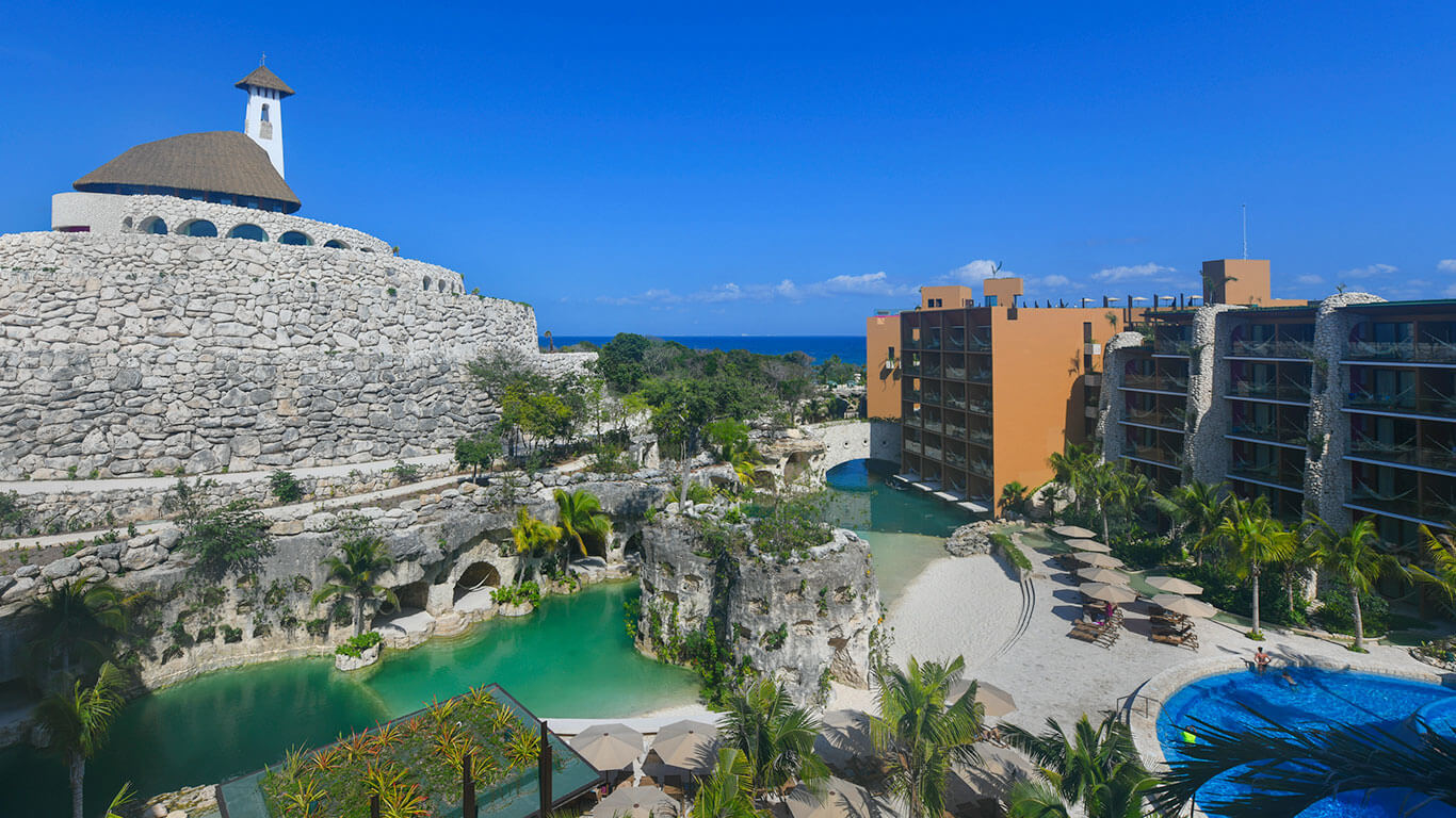view of the circular wedding chapel, cenote pools and buildings hotel xcaret