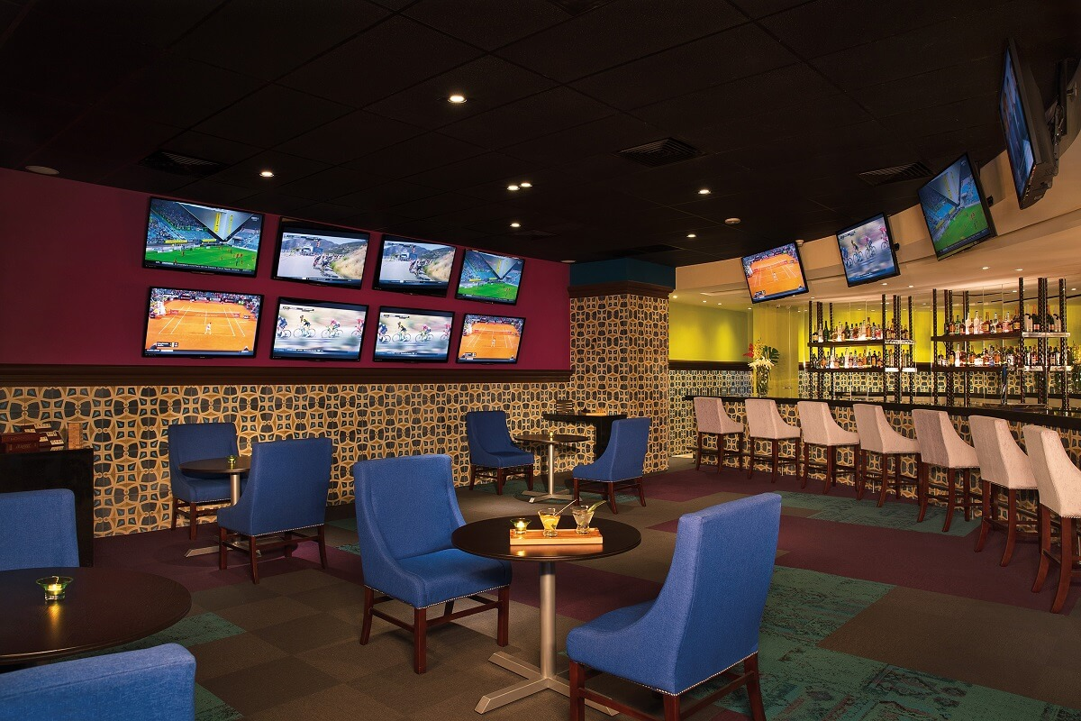 casino interior with many TV screens and a bar area