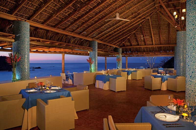ocean view restaurant with a thatched roof and square tables