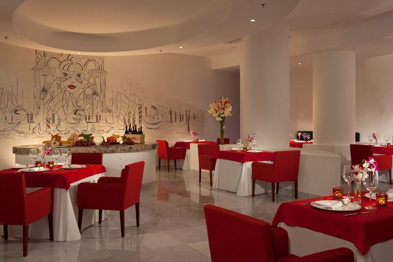 red and white chairs and linens in a modern restaurant at secrets huatulco