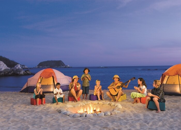 children around a beach campfire and tents set up at dusk