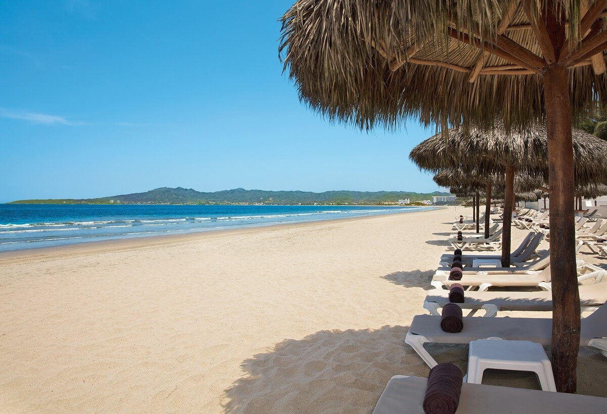 expanse of white sandy beach, palapas, loungers and mountains in the distance