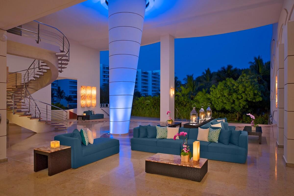 lobby area at dusk with blue sofas and lanterns dreams villamagna