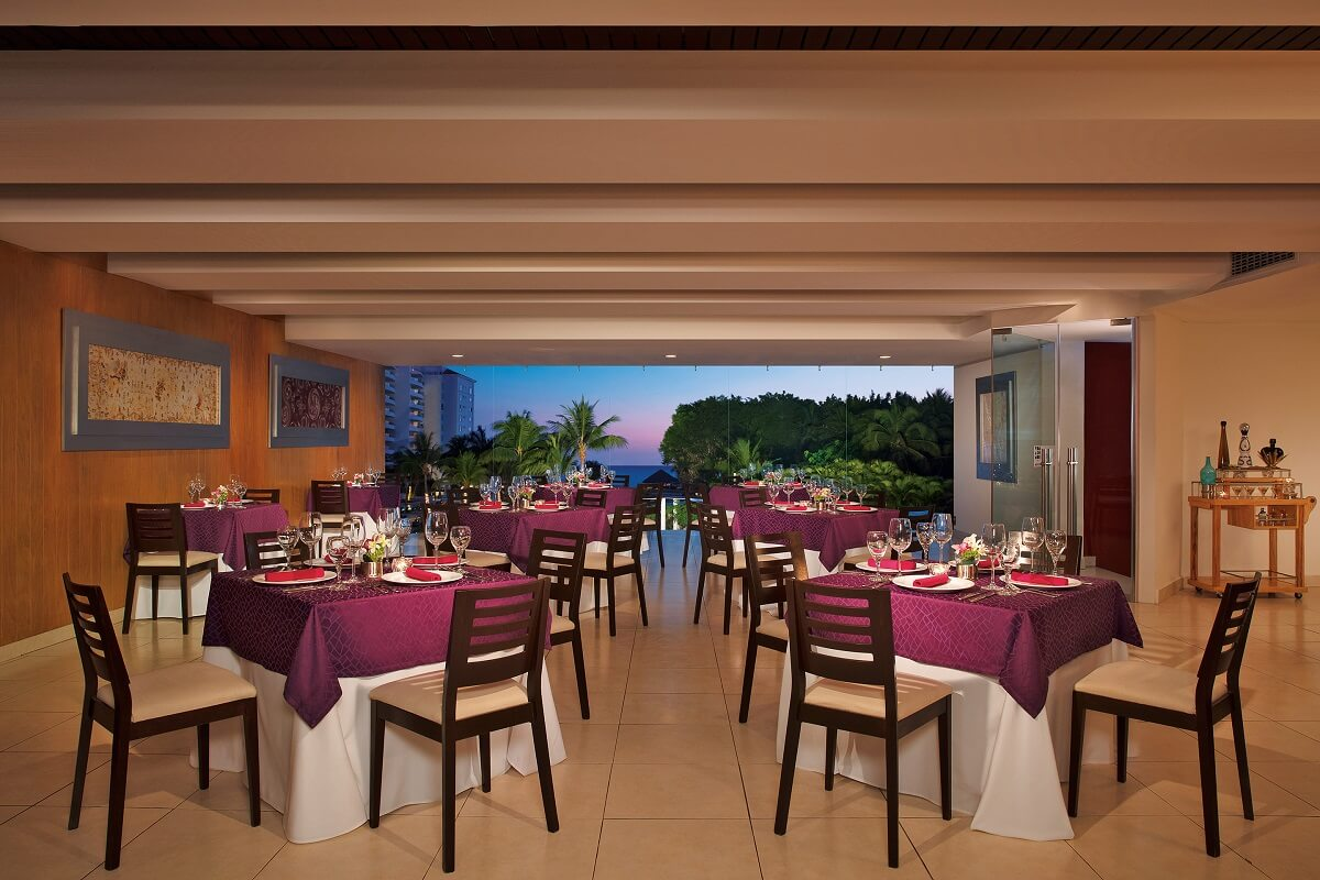 restaurant with purple tableclothes, an a large window with tropical views