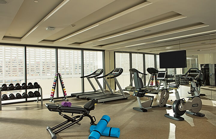 fitness center with treadmills, equipment and a mirrored wall