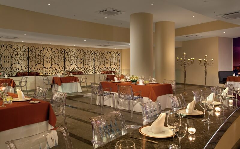 acrylic chairs, rust colored linens and set tables at the french restaurant secrets huatulco
