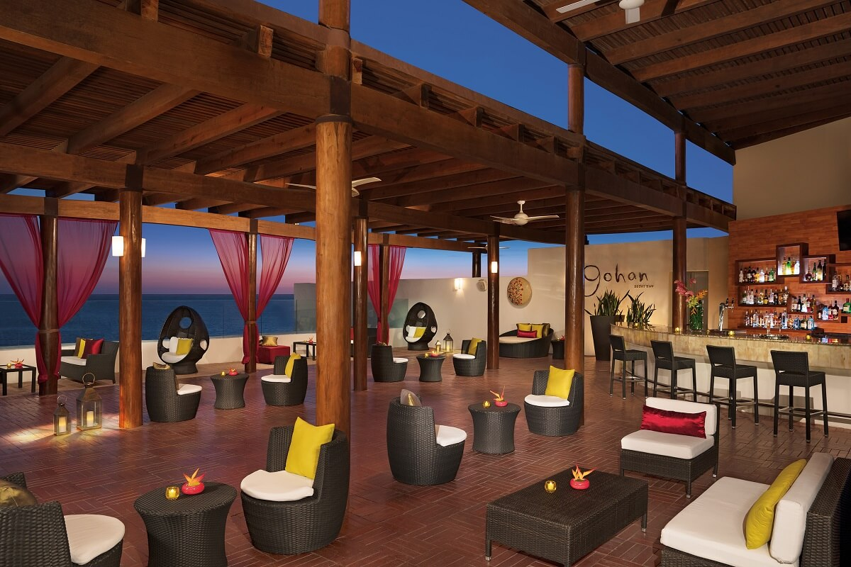 sky bar area with wicker furniture and yellow cushions