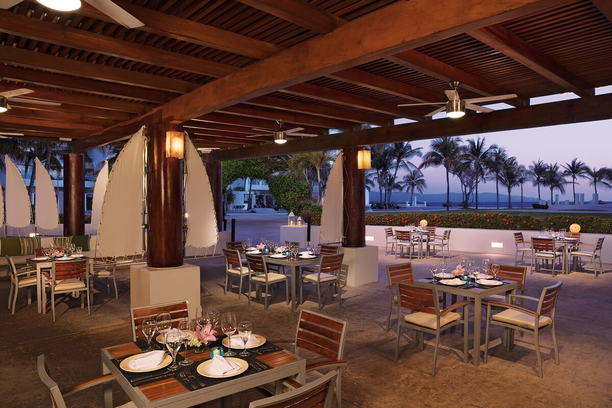 open air restaurant with wooden tables for 4