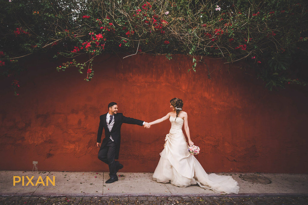 groom and bride holding hands in front of a runt colored wall