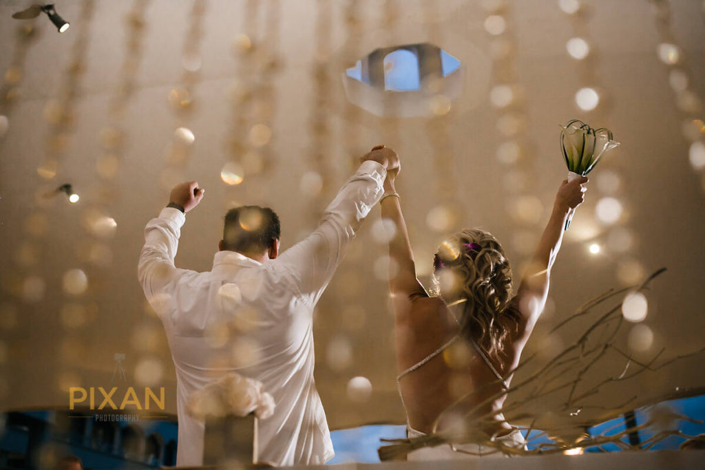 artistic wedding photo of bride and groom cheering