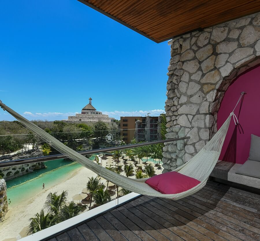hammock with pink cushion on balcony with river view hotel xcaret