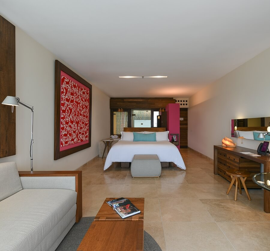 interior of a hotel room with a desk area and king bed at hotel xcaret