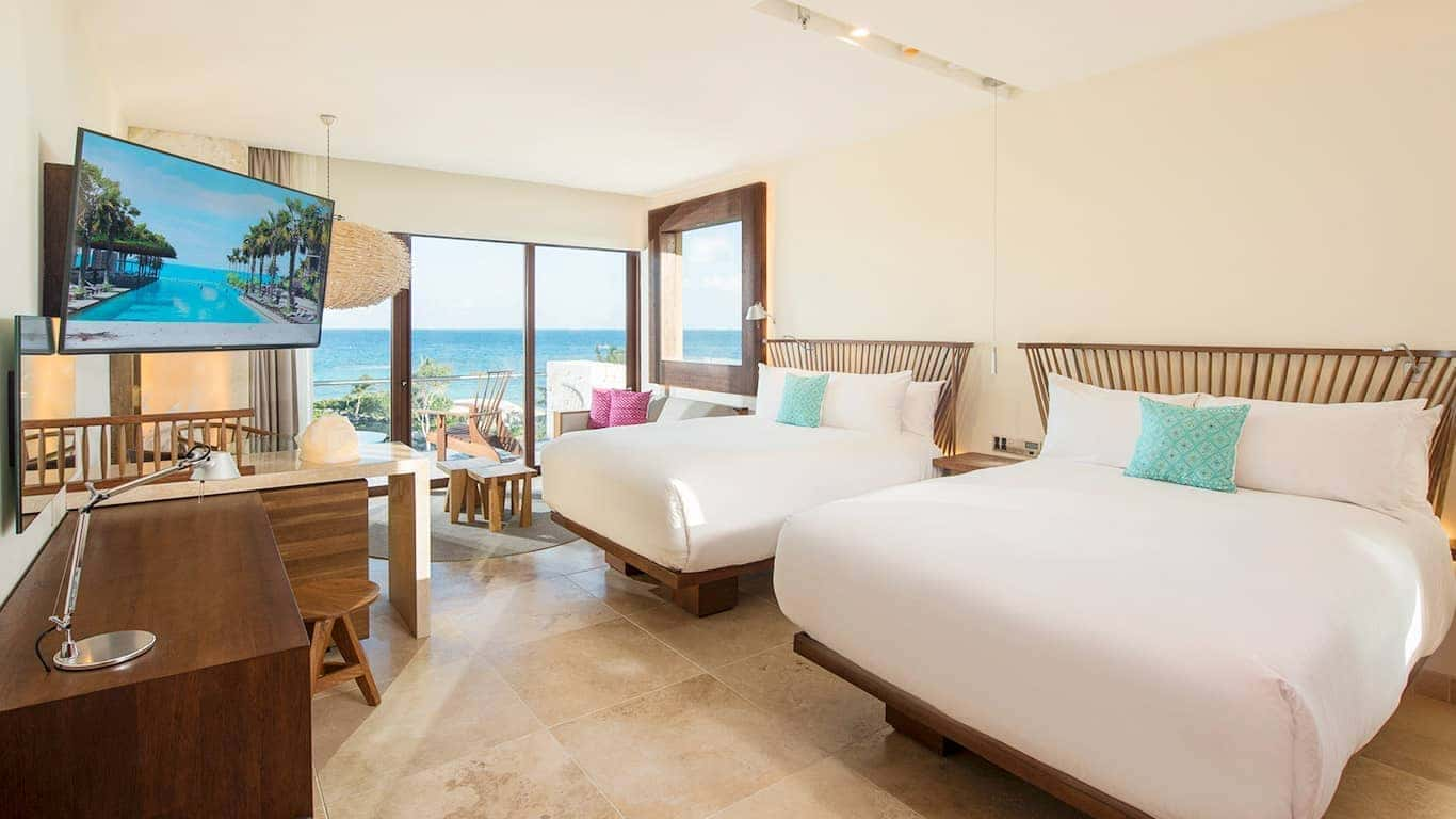 ocean view hotel room with two double beds and wood furniture