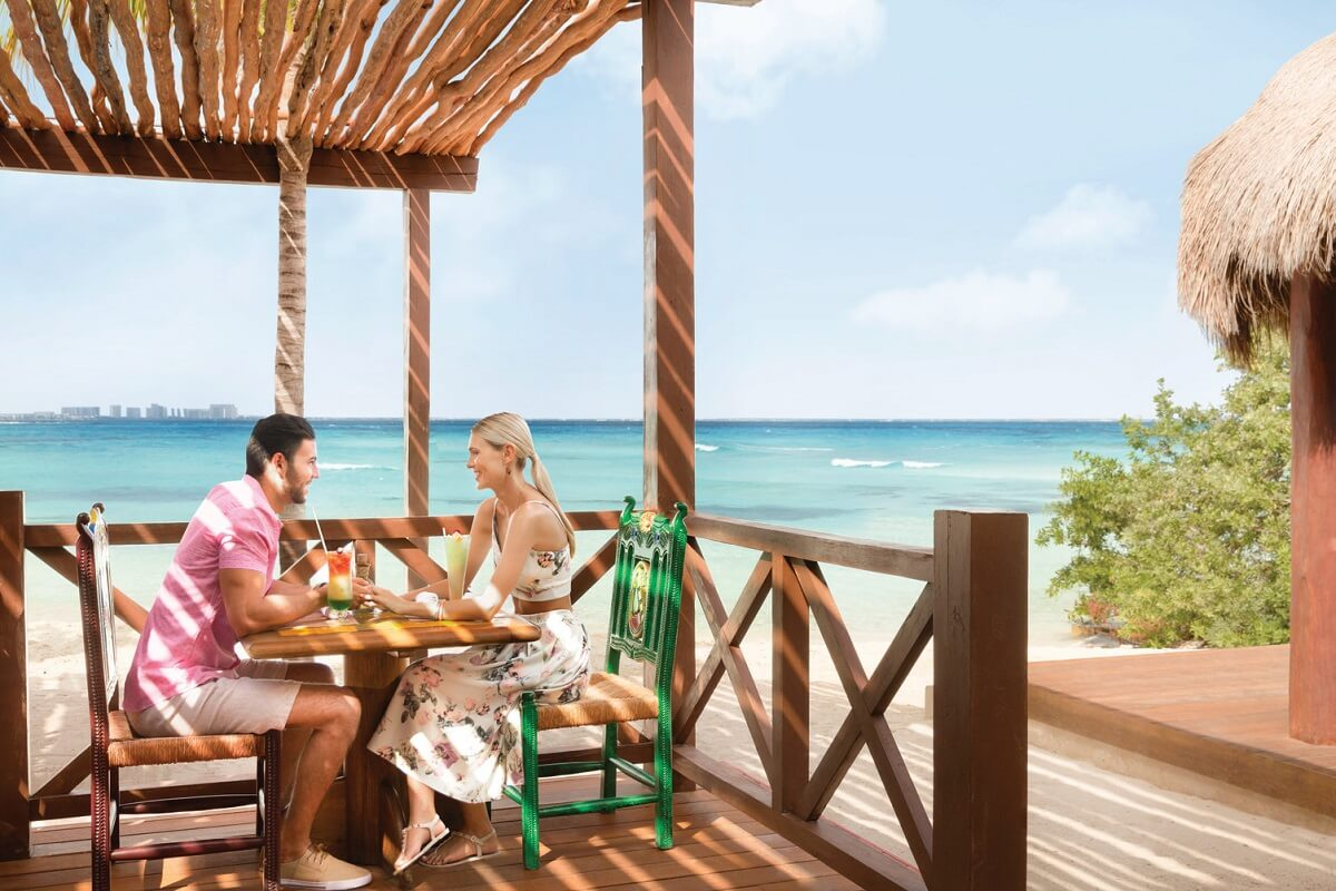 couple enjoying drinks at the beachfront restaurant hyatt ziva cancun