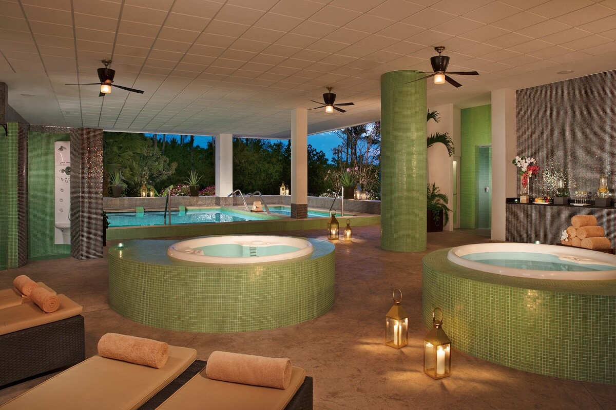 hydrotherapy area of a spa with green ceramic, ceiling fans and garden views