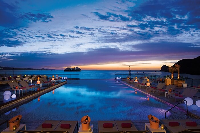 infinity pool at dusk with view of the bay in cabo san lucas