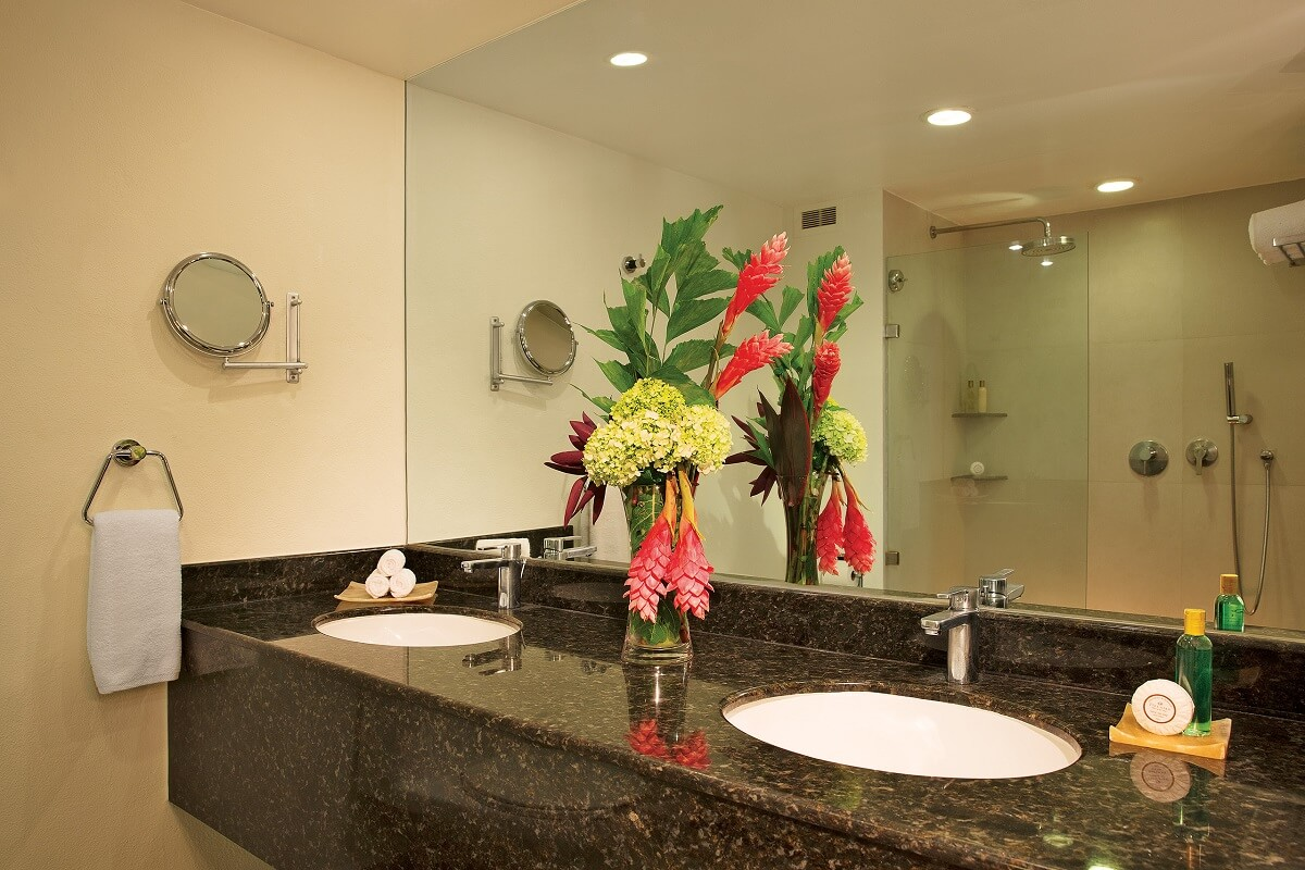 bathroom with double sinks and a flower arrangement