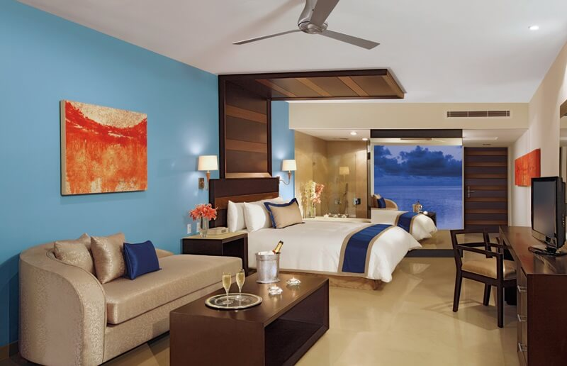 interior of hotel room with sofa, queen bed and wood furniture