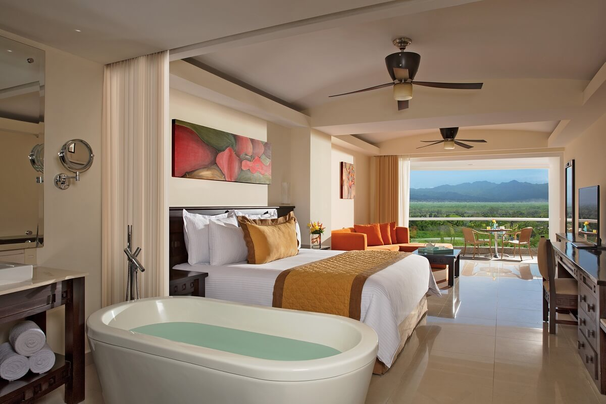 hotel room with garden views, a king bed, a bathtub