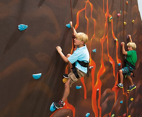 children with safety harnesses on a climbing wall