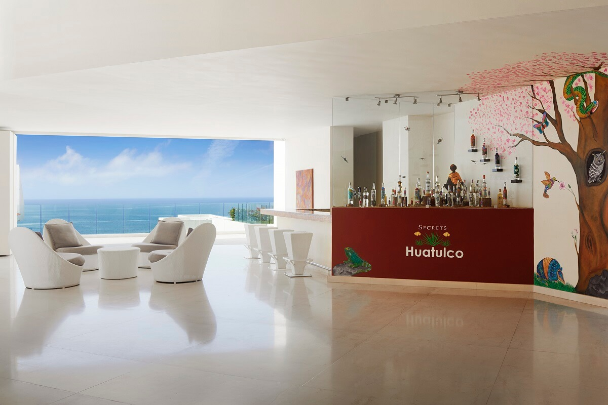 ocean view lobby bar area with white furniture and a mural of a tree