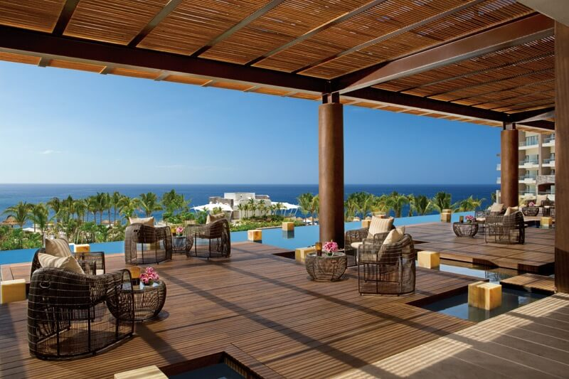wooden deck with wicker furniture with ocean views in the now amber lobby