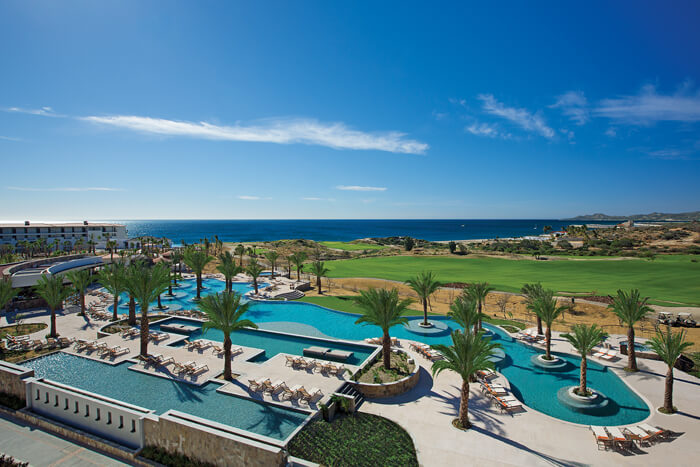 aerial view of the pool area and golf course with the ocean in the distance Secrets Los Cabos