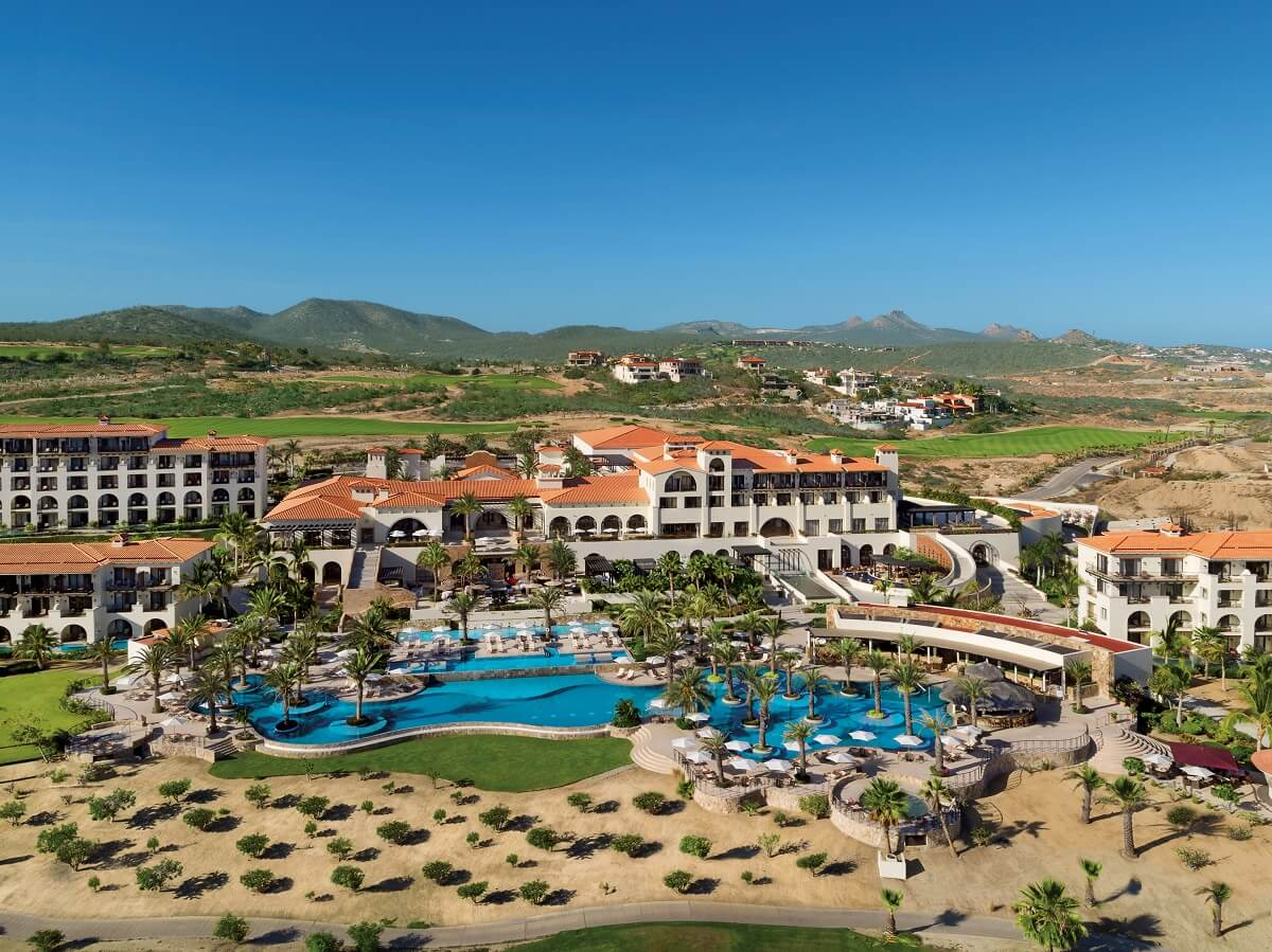 aerial view of the main pool area including the beach and mountains in the distance at secrets los cabos